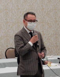 あいさつする平野代表幹事